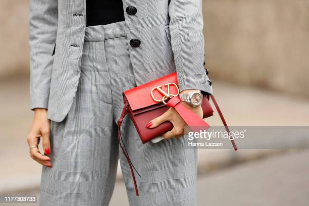 A guest wearing oversized glasses grey suit and Valentino clutch outside Gauchere during Paris Fashion Week Womenswear Spring Summer 2020 on...