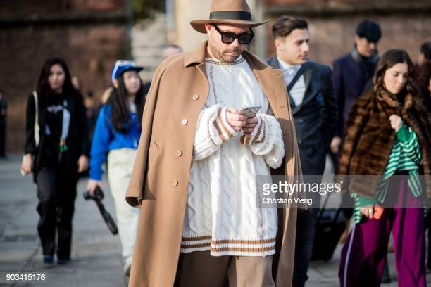 A guest wearing oversized knit brown wool coat hat is seen during the 93 Pitti Immagine Uomo at Fortezza Da Basso on January 10 2018 in Florence Italy