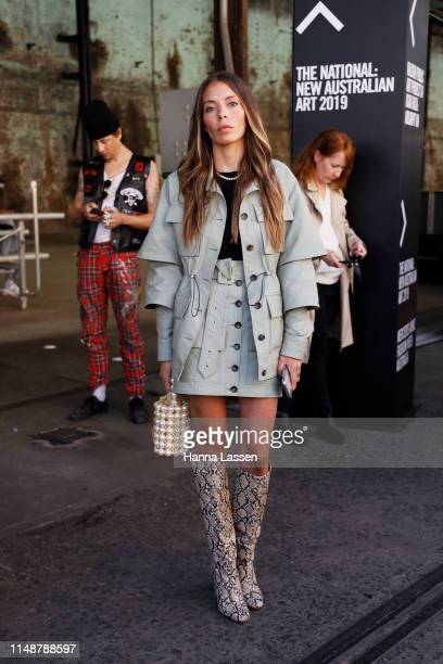 A guest wearing parka and skirt with snake print boots at MercedesBenz Fashion Week Resort 20 Collections on May 13 2019 in Sydney Australia