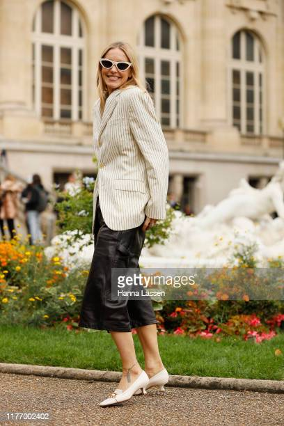 A guest wearing pin striped blazer leather shorts and white shoesoutside Maison Margiela on September 25 2019 in Paris France