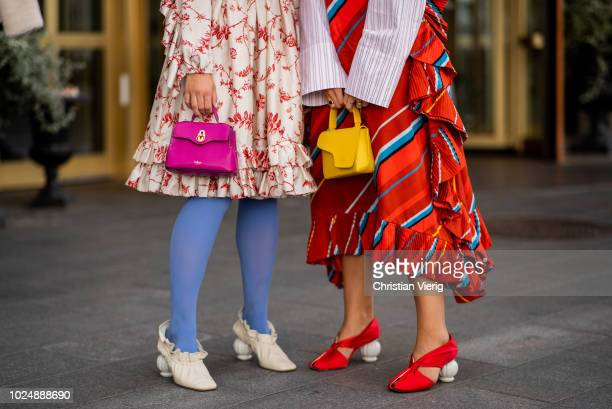A guest wearing pink bag and a guest wearing yellow bag seen during Stockholm Runway SS19 on August 28 2018 in Stockholm Sweden