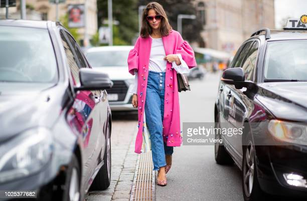 A guest wearing pink coat denim jeans during Stockholm Runway SS19 on August 30 2018 in Stockholm Sweden