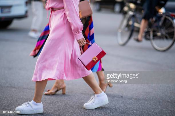 A guest wearing pink dress and bag white sneakers is seen outside Saks Potts during the Copenhagen Fashion Week Spring/Summer 2019 on August 9 2018...