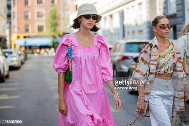 A guest wearing pink dress green Jacquemus bag is seen outside Malaikaraiss during Copenhagen Fashion Week SS21 on August 10 2020 in Copenhagen...