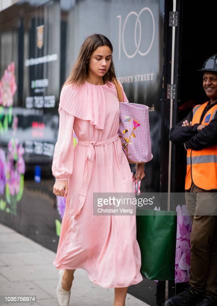 A guest wearing pink dress shopping bag is seen outside Natasha Zinko during London Fashion Week September 2018 on September 18 2018 in London England