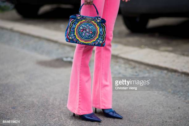 A guest wearing pink flared pants bag detail outside Fendi during Milan Fashion Week Fall/Winter 2017/18 on February 23 2017 in Milan Italy
