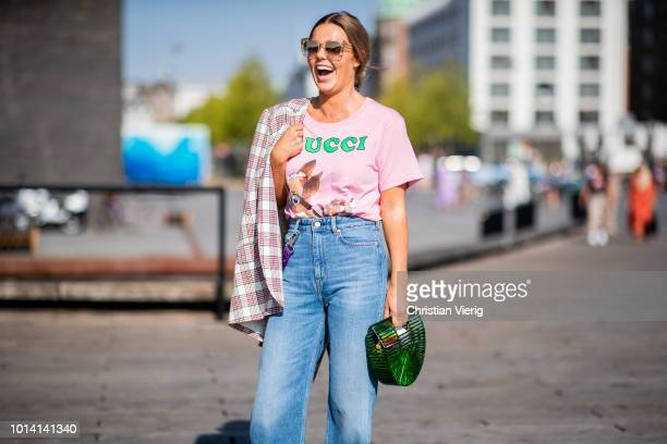 Guest wearing pink Gucci tshirt, denim jeans, green Cult Gaia bag seen outside Munthe during the Copenhagen Fashion Week Spring/Summer 2019 on August...