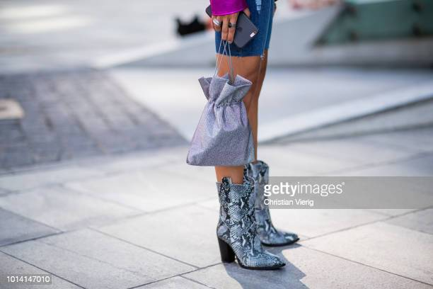 A guest wearing pink jacket skinny denim shorts snake print boots is seen outside Designers Remix during the Copenhagen Fashion Week Spring/Summer...