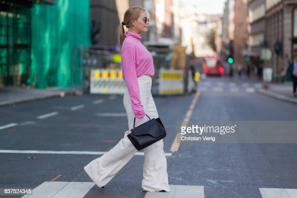 Guest wearing pink knit, white pants outside Line of Oslo on August 22, 2017 in Oslo, Norway.