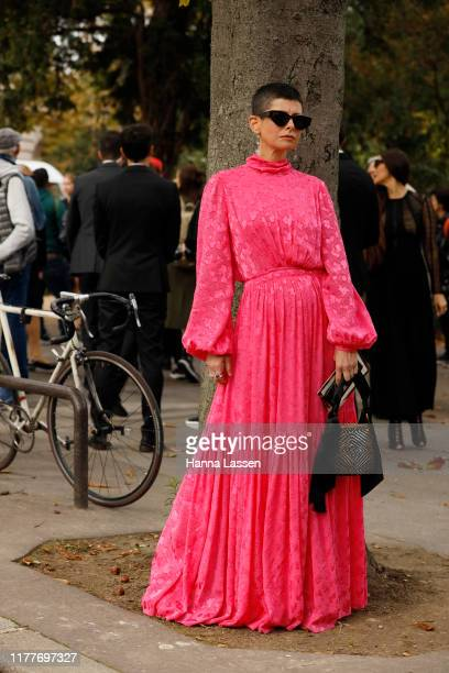 Guest wearing pink maxi pleated dress and black clutch outside the Elie Saab show during Womenswear Spring/Summer 2020 show Paris Fashion Week on...