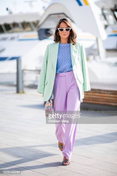 A guest wearing pink pants blue knit green blazer is seen during Stockholm Runway SS19 on August 29 2018 in Stockholm Sweden