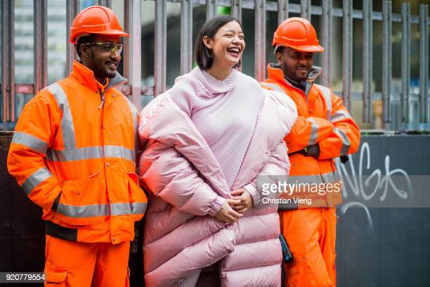 A guest wearing pink puffer jacket standing in between two construction workers seen outside Marques Almeida during London Fashion Week February 2018...