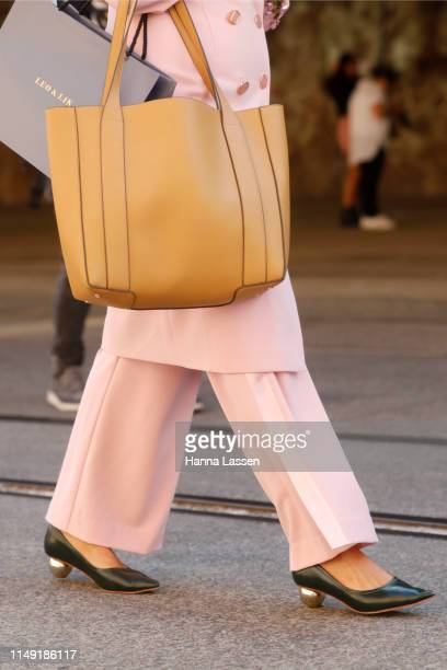 A guest wearing pink suit and beige leather bag at MercedesBenz Fashion Week Resort 20 Collections on May 15 2019 in Sydney Australia