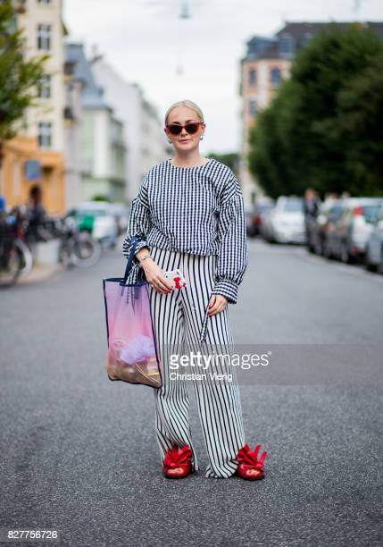 A guest wearing plaid longshirt striped wide leg pants sheer bag red sandals outside Designers Nest on August 8 2017 in Copenhagen Denmark