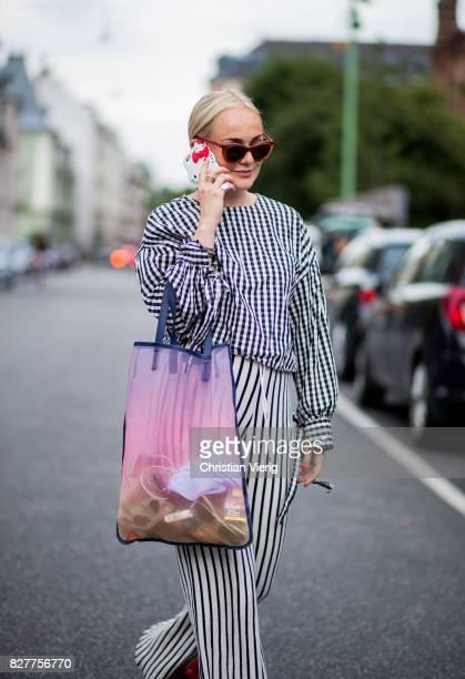 A guest wearing plaid longshirt striped wide leg pants sheer bag red sandals outside Designers Nest on August 8 2017 in Copenhagen Denmark