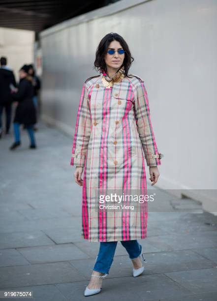 A guest wearing plaid pink coat seen outside Burberry during London Fashion Week February 2018 on February 17 2018 in London England