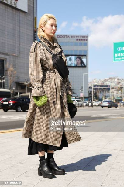Guest wearing plaid trench coat and black maxi skirt with belt bag is seen at the Seoul Fashion Week 2019 F/W at Dongdaemun Design Plaza at...