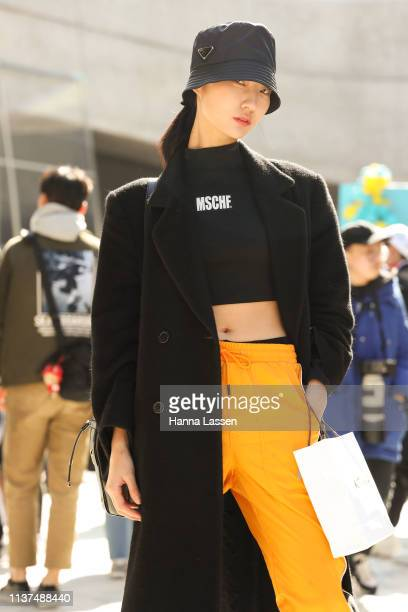 Guest wearing Prada bucket hat black cropped tshirt black long coat and yellow pants with Adidas knee high sneakers is seen at the Hera Seoul Fashion...