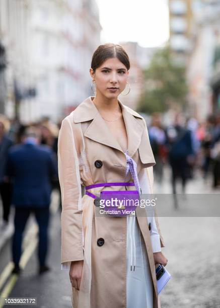 A guest wearing purple belt bag beige coat white pants is seen outside Molly Goddard during London Fashion Week September 2018 on September 15 2018...