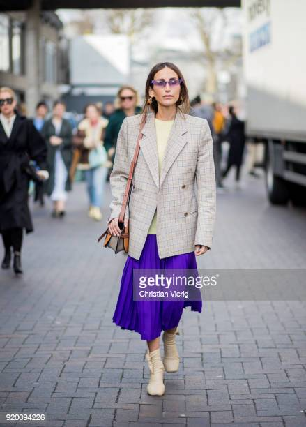 A guest wearing purple skirt plaid blazer jacket Loewe bag seen outside Roland Mouret during London Fashion Week February 2018 on February 18 2018 in...