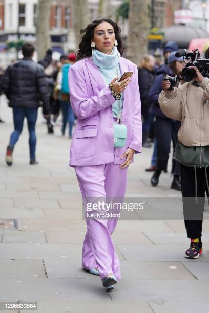 Guest wearing purple trouser suit attends Erdem at National Portrait Gallery during London Fashion Week February 2020 on February 17, 2020 in London,...