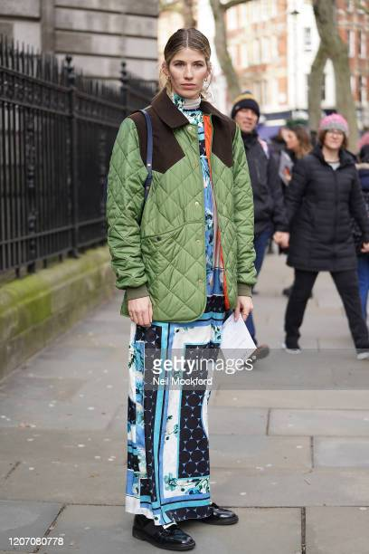 Guest wearing quilted coat and blue scarf print dress attends Erdem at National Portrait Gallery during London Fashion Week February 2020 on February...