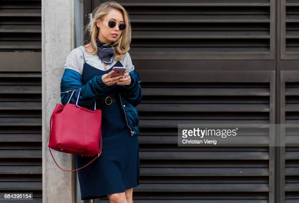 A guest wearing red bag bandana navy dress bomber jacket at day 5 during MercedesBenz Fashion Week Resort 18 Collections at Carriageworks on May 18...
