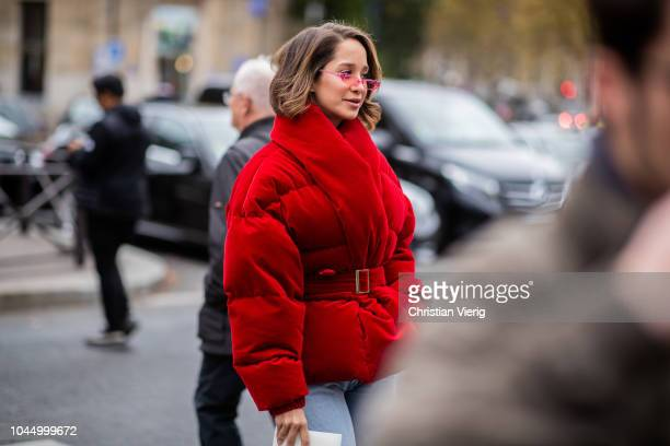 A guest wearing red belted down feather jacket is seen outside Miu Miu during Paris Fashion Week Womenswear Spring/Summer 2019 on October 2 2018 in...
