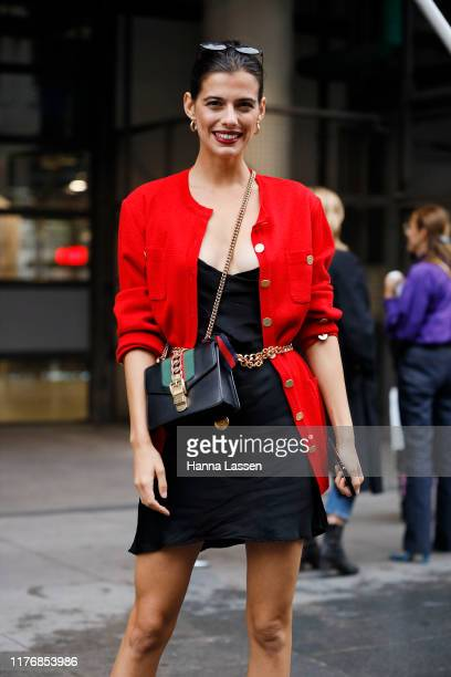 A guest wearing red cardigan with Chanel chain belt and Gucci bag outside Koche on September 24 2019 in Paris France