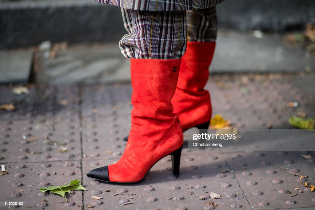 A guest wearing red Chanel boots outside Pringle of Scotland during London Fashion Week September 2017 on September 18, 2017 in London, England.