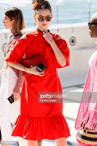 A guest wearing red dress and red leather clutch at MercedesBenz Fashion Week Resort 20 Collections on May 16 2019 in Sydney Australia