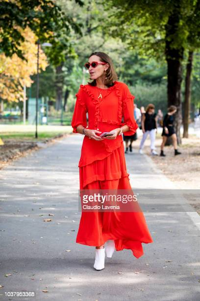 A guest wearing red dress and white heels boots is seen before the Philosophy by Lorenzo Serafini show during Milan Fashion Week Spring/Summer 2019...