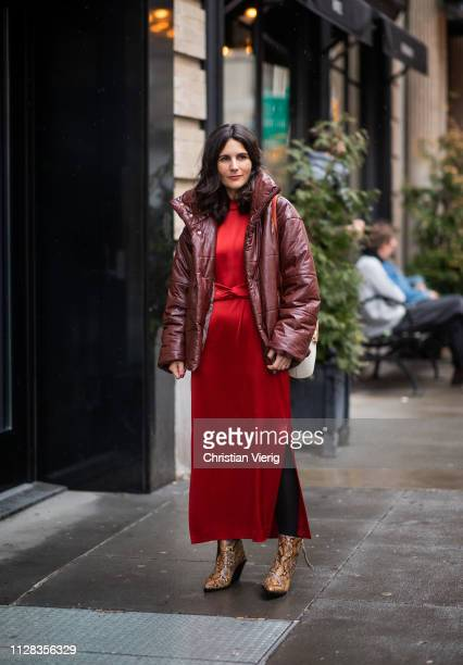 A guest wearing red dress puffer jacket outside Nanushka during New York Fashion Week Autumn Winter 2019 on February 08 2019 in New York City