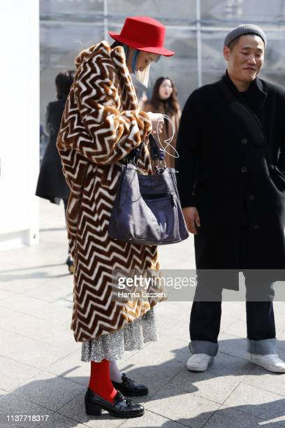 Guest wearing red felt hat brown and white faux fur coat and red and white mixmatching socks is seen at the Hera Seoul Fashion Week 2019 F/W at...