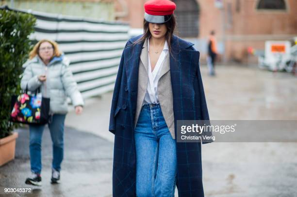 A guest wearing red flat cap navy checked wool coat denim jeans is seen during the 93 Pitti Immagine Uomo at Fortezza Da Basso on January 9 2018 in...