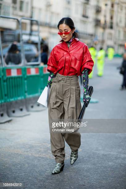 A guest wearing red leather button shirt olive high waist pants black ling bag gloves is seen outside Simone Rocha during London Fashion Week...