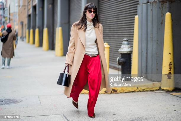 A guest wearing red pants beige wool coat black bag creme white turtleneck seen outside Ralph Lauren on February 12 2018 in New York City