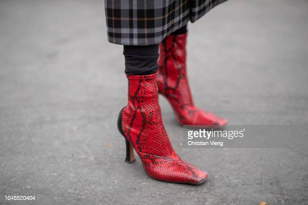 A guest wearing red snake print ankle boots is seen outside Chanel during Paris Fashion Week Womenswear Spring/Summer 2019 on October 2 2018 in Paris...