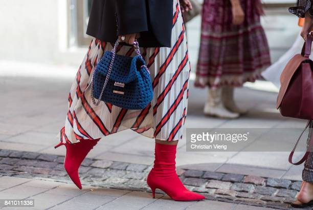 A guest wearing red sock boots by Malene Birger skirt Stella Mc Cartney bag outside Busnel on August 30 2017 in Stockholm Sweden