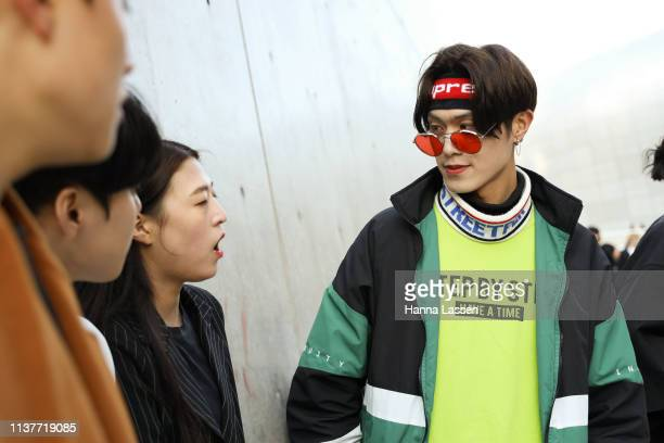 Guest wearing red sunglasses neon green jumper and black and green blocked jacket is seen at the Hera Seoul Fashion Week 2019 F/W at Dongdaemun...