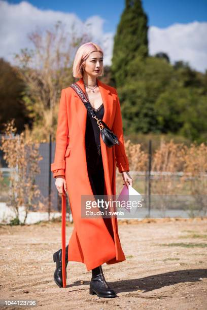 Guest wearing red trench coat is seen before the Christian Dior show on September 24 2018 in Paris France