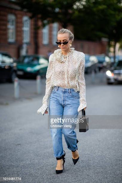 A guest wearing ruffled blouse denim jeans is seen outside Saks Potts during the Copenhagen Fashion Week Spring/Summer 2019 on August 9 2018 in...