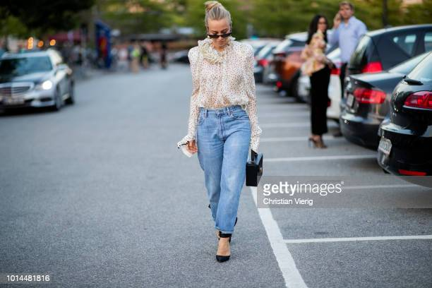 Guest wearing ruffled blouse, denim jeans is seen outside Saks Potts during the Copenhagen Fashion Week Spring/Summer 2019 on August 9, 2018 in...