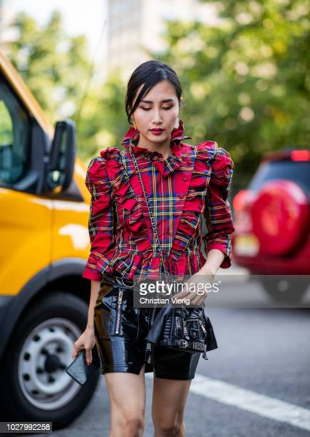 A guest wearing ruffled red black checked top Moschino bag is seen outside Noon By Noor during New York Fashion Week Spring/Summer 2019 on September...