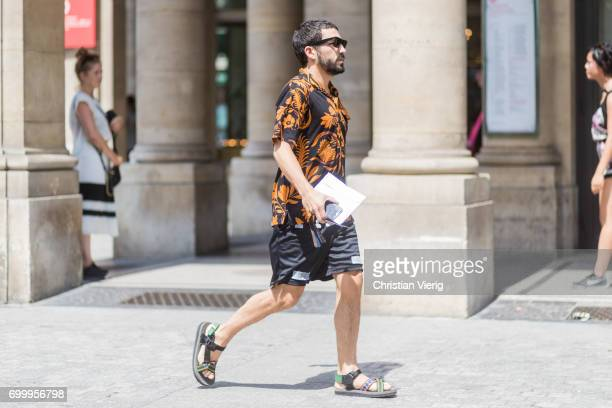 A guest wearing sandals button shirt with short sleeves outside Louis Vuitton during Paris Fashion Week Menswear Spring/Summer 2018 on June 22 2017...