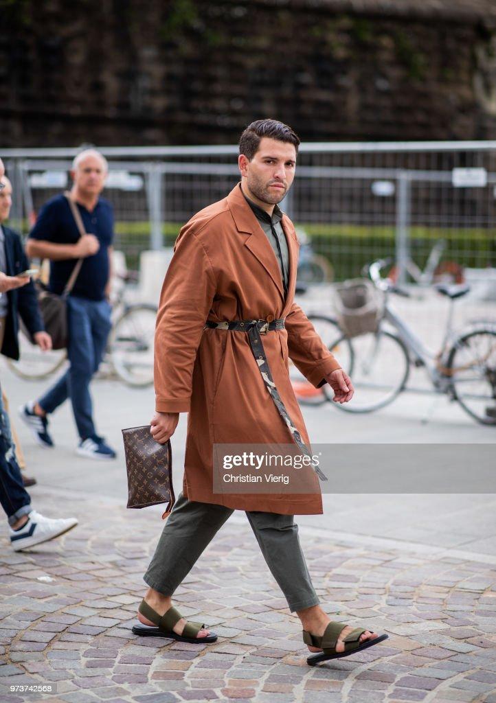 ec6732ee7b A guest wearing sandals, Louis Vuitton clutch, trench coat is seen ...