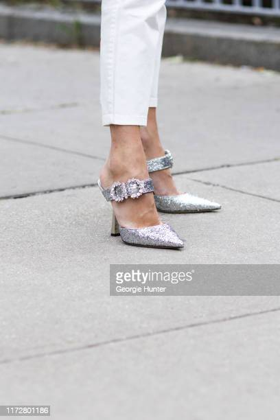 Guest wearing silver sandals with gem detail buckle and white pants on September 06, 2019 in New York City.