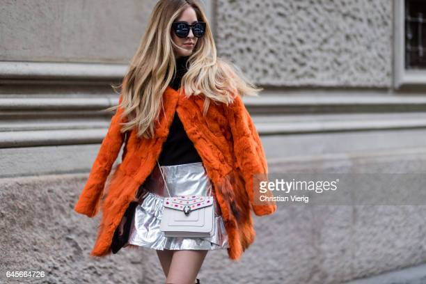 A guest wearing silver skirt orange fake fur coat outside Salvatore Ferragamo during Milan Fashion Week Fall/Winter 2017/18 on February 26 2017 in...