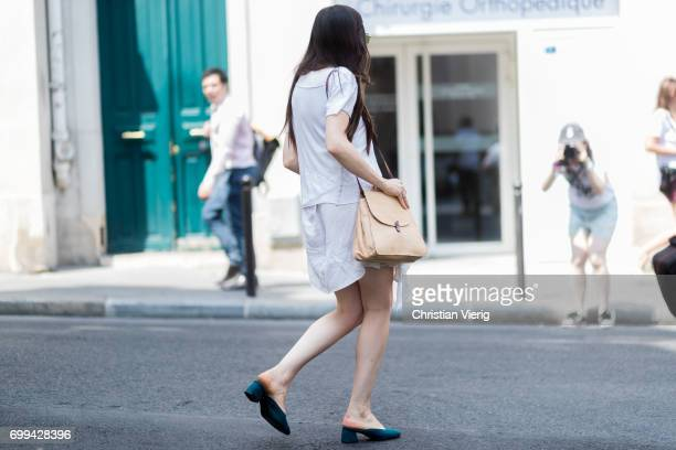 A guest wearing slippers white dress brown bag outside Lemaire during Paris Fashion Week Menswear Spring/Summer 2018 on June 21 2017 in Paris France