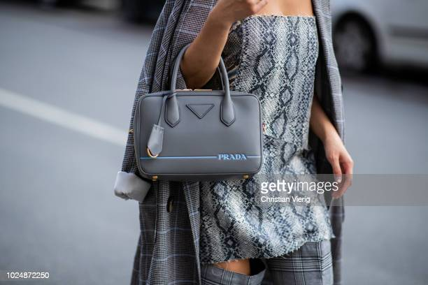 A guest wearing snake print dress Prada bag overknees grey checked jacket worn over the shoulders is seen during Stockholm Runway SS19 on August 28...
